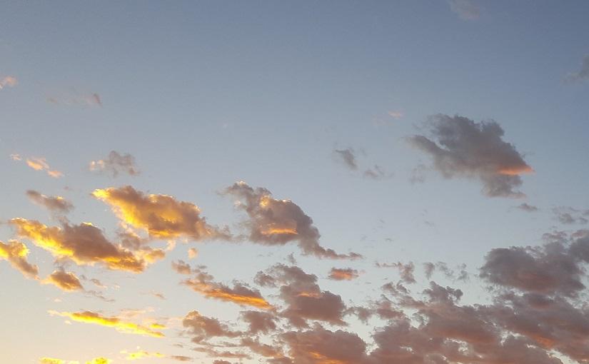 Sun lighting clouds across sky