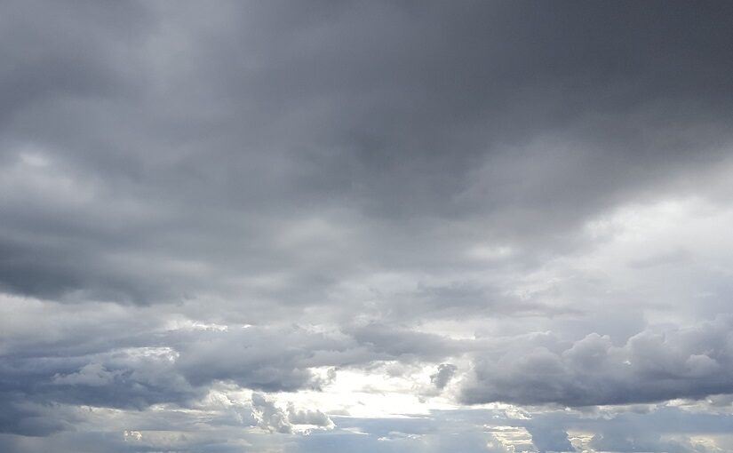Grey clouded sky with light behind