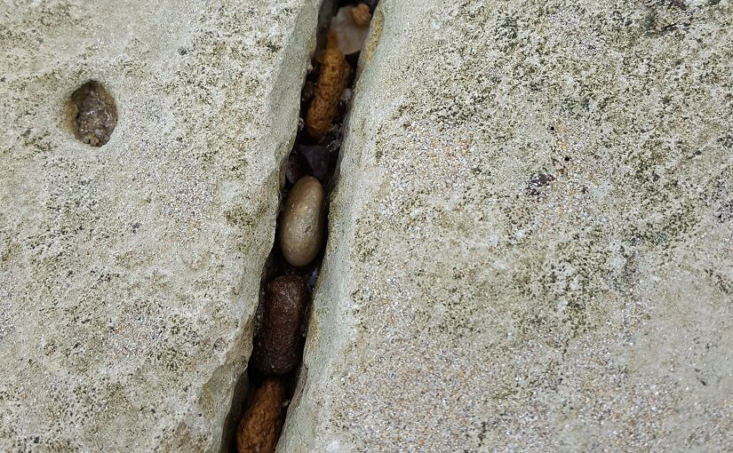 Pebbles lodged in crack of rock
