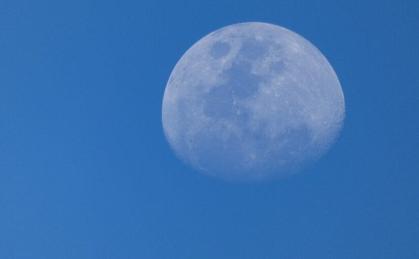 Partial moon against blue sky