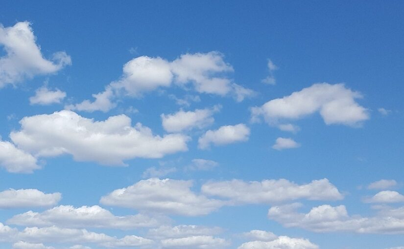 White clouds drifting against fading blue sky