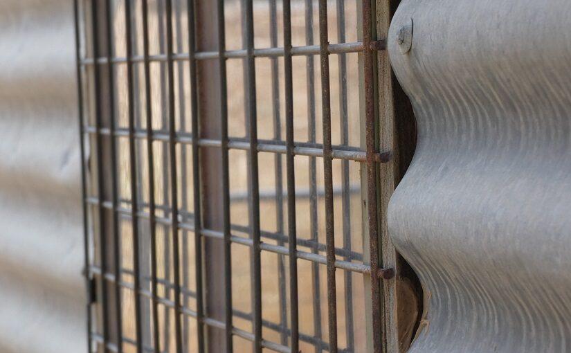 Bars over window on corrugated iron wall